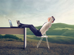Business Man Relaxing in Field with Desk