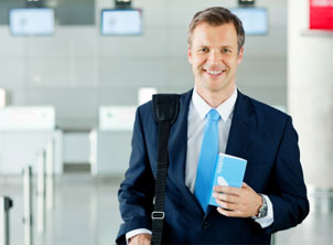 Businessman Holding Ticket In Airport-Horizontal