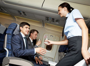 Flight Attendant Handing Water to Business Man