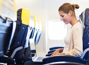 Young Woman Working on Laptop on Plane